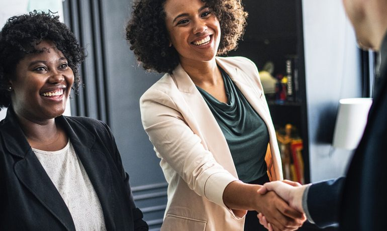 Two women ending meeting with handshake with third person