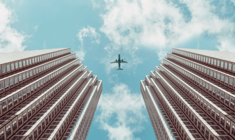 Airplane in the sky between two buildings from below