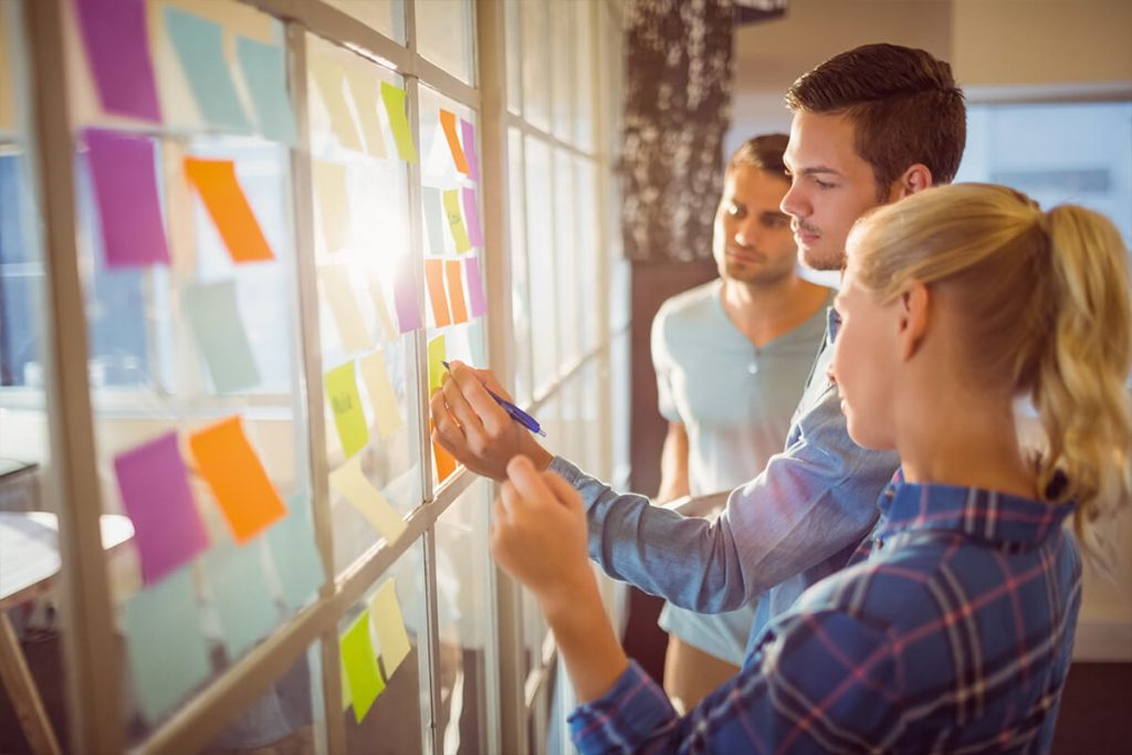 Three young professionals work together to brainstorm on sticky notes